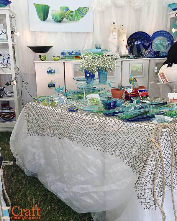 Handmade glass tableware on display in a nautical-themed craft booth.