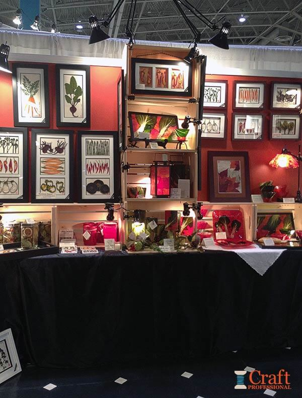 Framed prints displayed on tables covered with black fabric