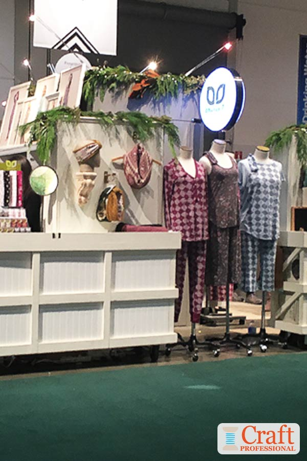 Three mannequins in a row displaying handmade pajamas in a craft booth demonstrate the display concept of arranging items in odd numbered groups.