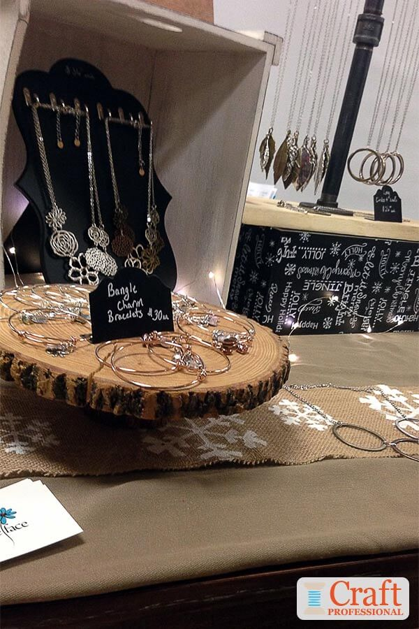 Handmade jewelry on  a tabletop display lit up with string lights.