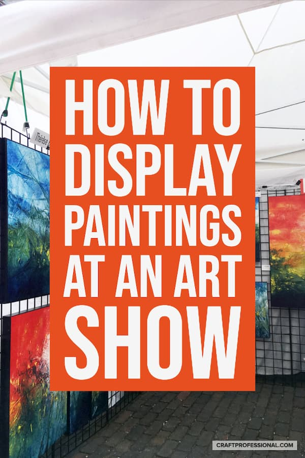 Paintings on display at a craft show. Text overlay - How to display paintings at an art show.