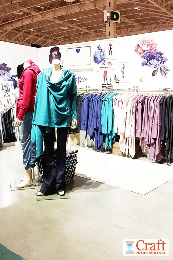 Colorful handmade clothing on display at a craft show. Two mannequins at the front of the display are angled to face shoppers approaching the booth from different sides.
