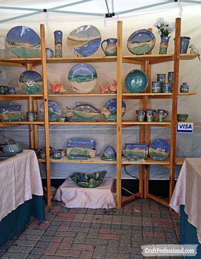 Foldable shelves display handmade pottery.