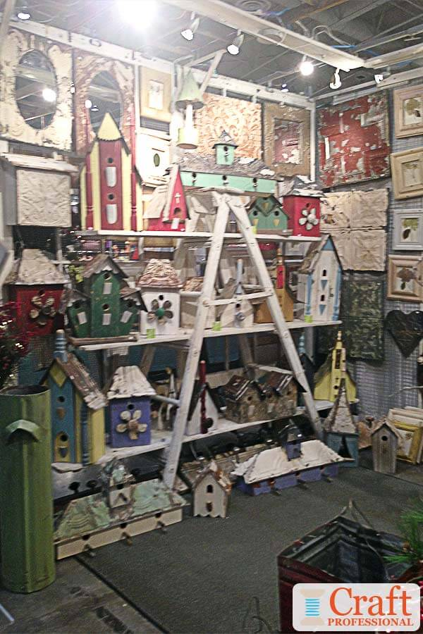 Handmade garden decor displayed on a ladder style shelf at a craft show.