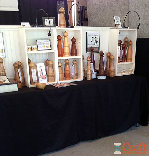 Handmade salt and pepper mills at a craft show.