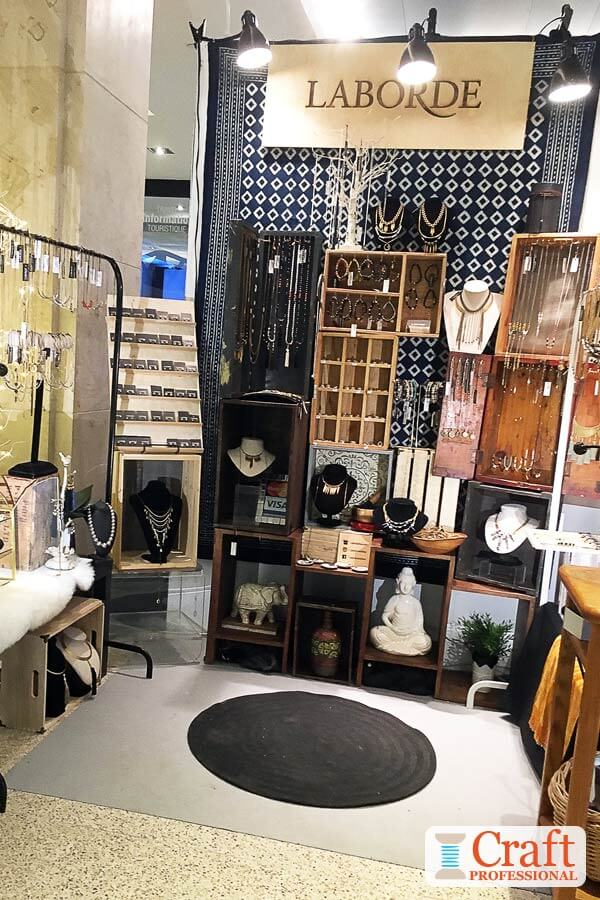 Handmade jewelry displayed in portable crates with overhead lighting.