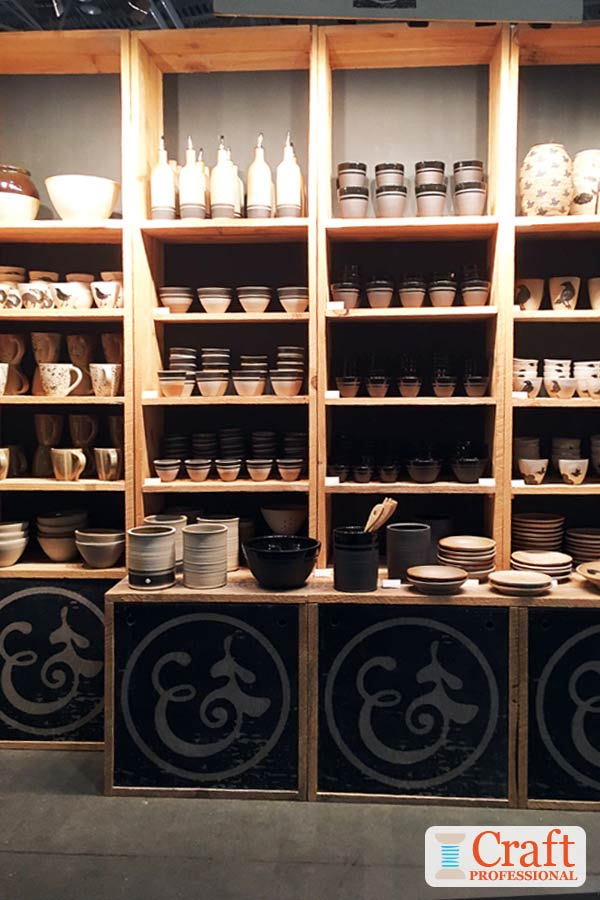 Handmade black and cream tableware displayed on tall wooden shelves at a craft show demonstrates the important of avoiding overcrowding your booth.