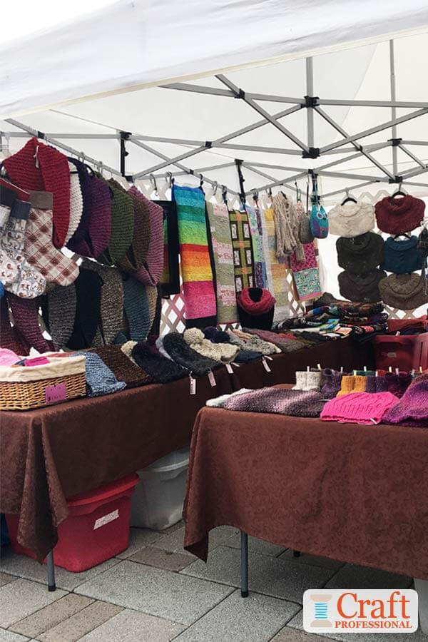 Hand knit accessories displayed in a craft tent at an outdoor farmers market.
