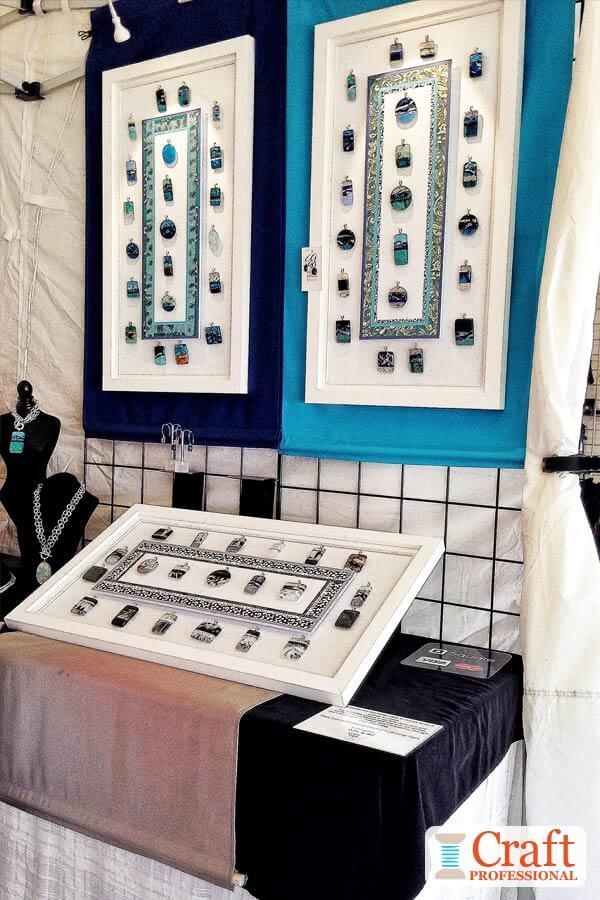 Handmade pendants displayed at a craft show.