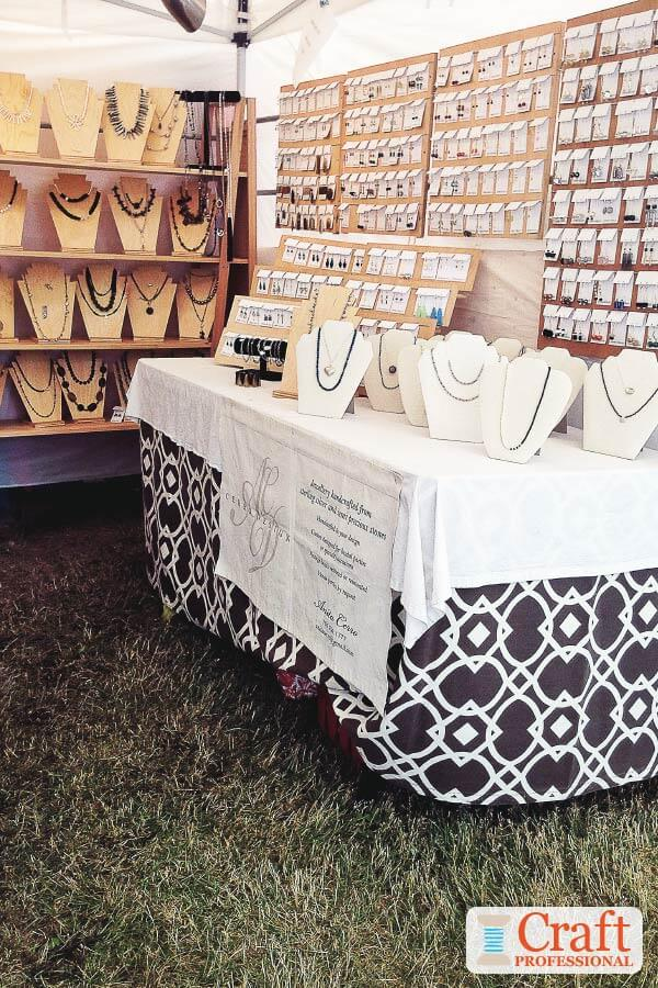 Handmade jewelry displayed on tabletops and shelves at an outdoor craft show. Necklaces are displayed on natural wood stands.