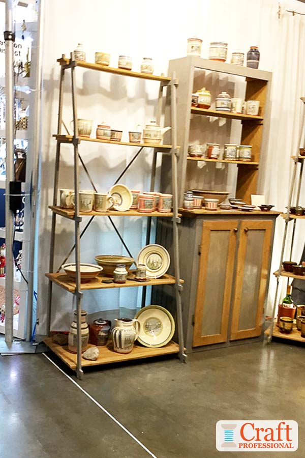 Handmade pottery on display on a shelf and a sideboard at a craft show demonstrates the importance of avoiding overcrowding your display.
