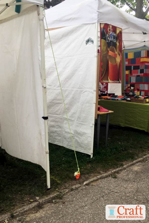 Craft tent anchored to grass with tent stake at an outdoor craft show.