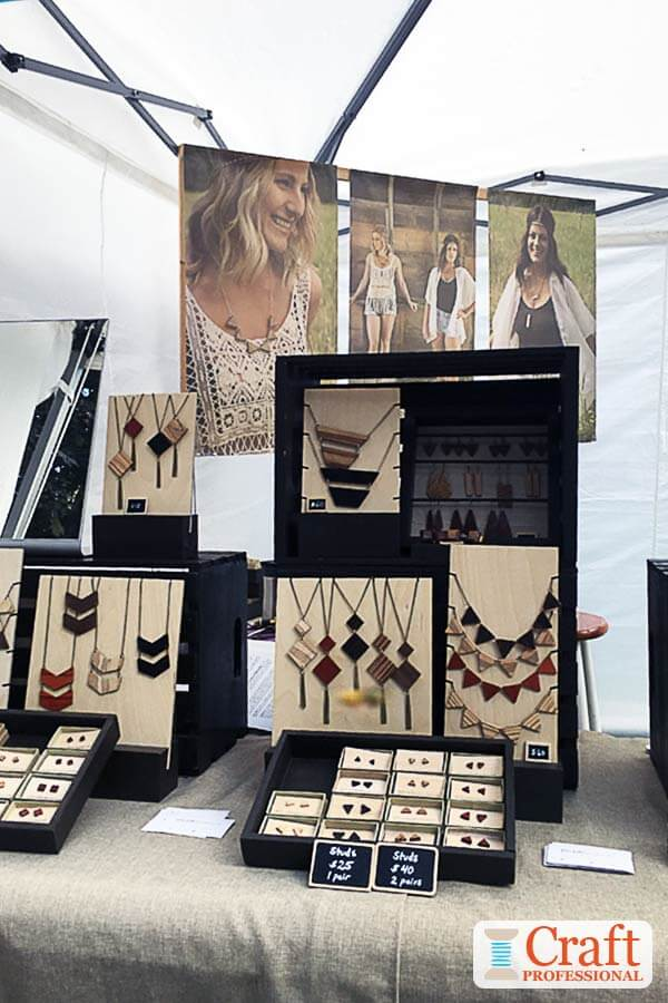 Handmade jewelry displayed on a table in matching wood crates.