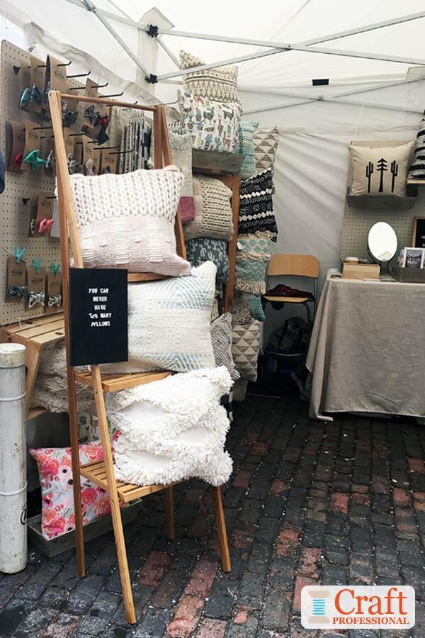Handmade pillows on display at an outdoor craft show