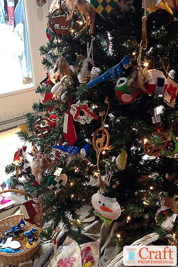 Christmas tree decorated with handmade ornaments at a craft show.