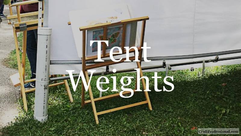 DIY tent weight made from PVC pipe attached to a tent at an outdoor craft show. Text overlay - Tent Weights.