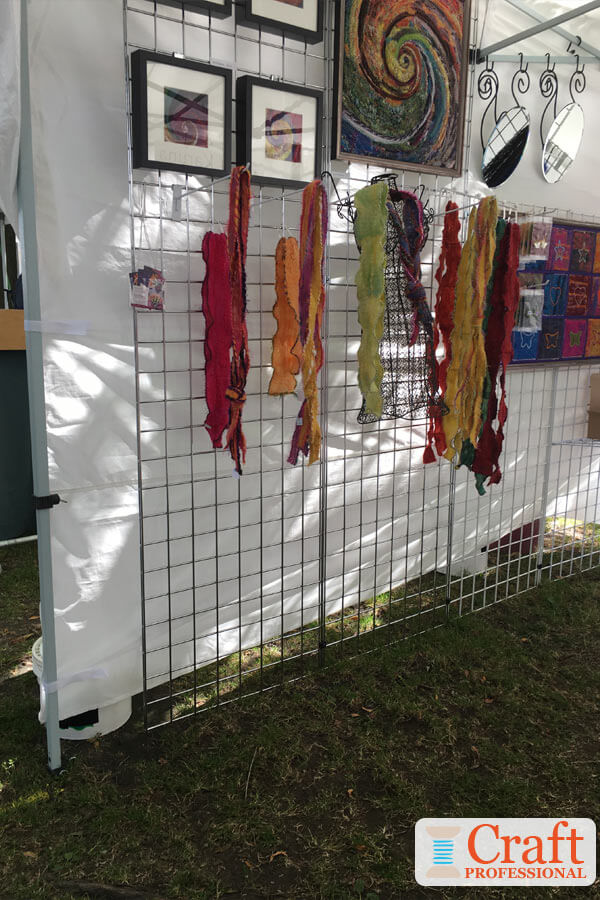 Colorful scarves and art displayed together in a craft tent at an outdoor show.