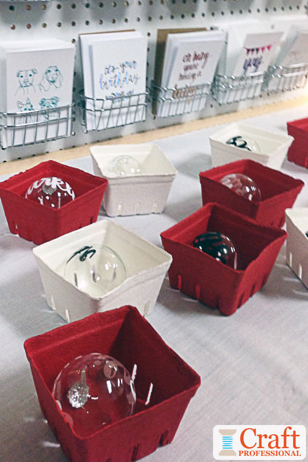 Handmade glass Christmas ornaments displayed in berry boxes painted red and white