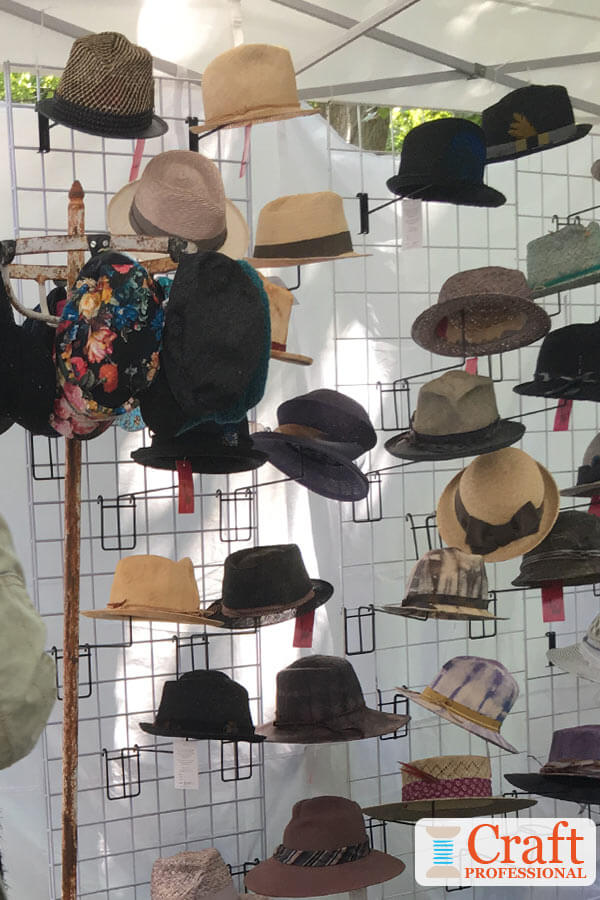 Handmade hats displayed in a on a gridwall system in a craft tent at an outdoor art fair.