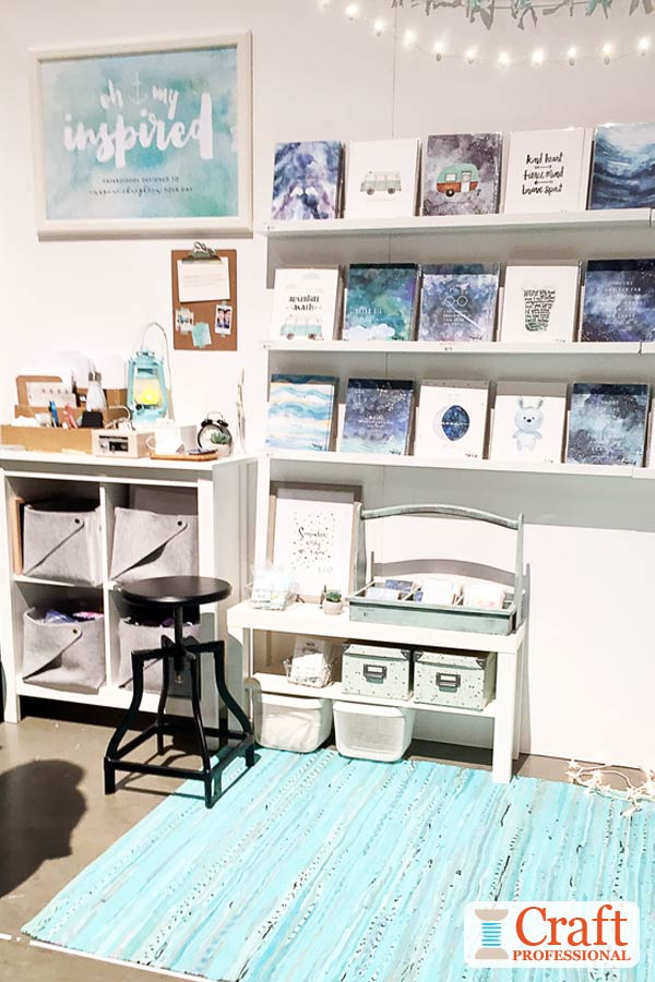 Watercolor art prints and cards in shades of blue on display at a craft show. Large booth sign painted in the same style shows the artist's aesthetic.