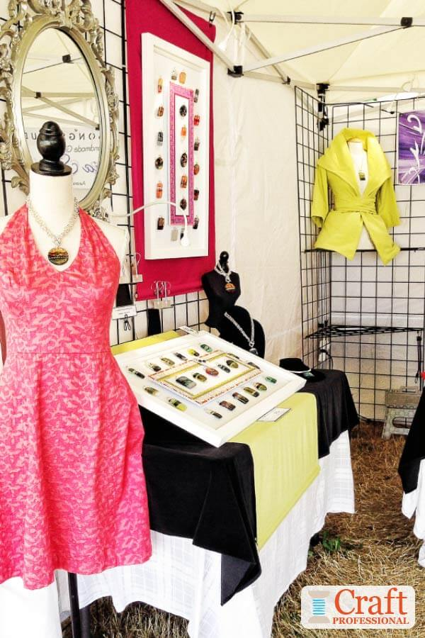 Mannequin in a pink dress displaying handmade pendant at a craft show.