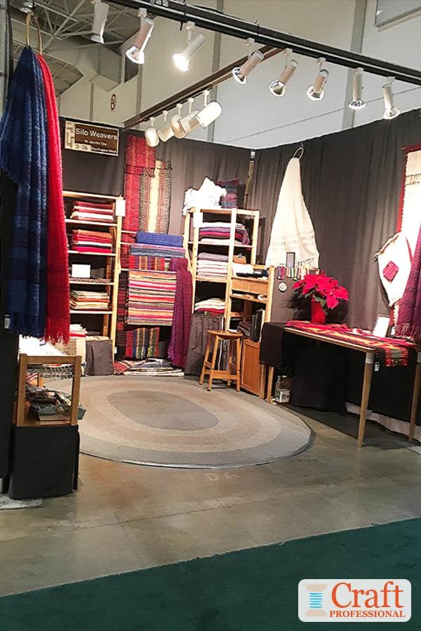 Handmade textiles displayed in a craft booth. Lights are secured overhead with approximately on light per foot.