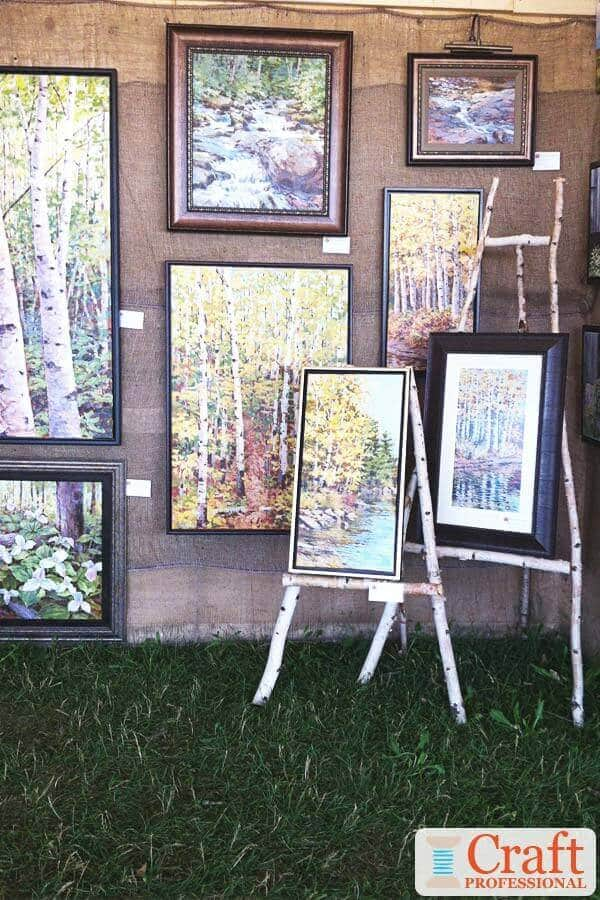 Paintings of birch trees displayed at an outdoor craft show on DIY birch wood easels.