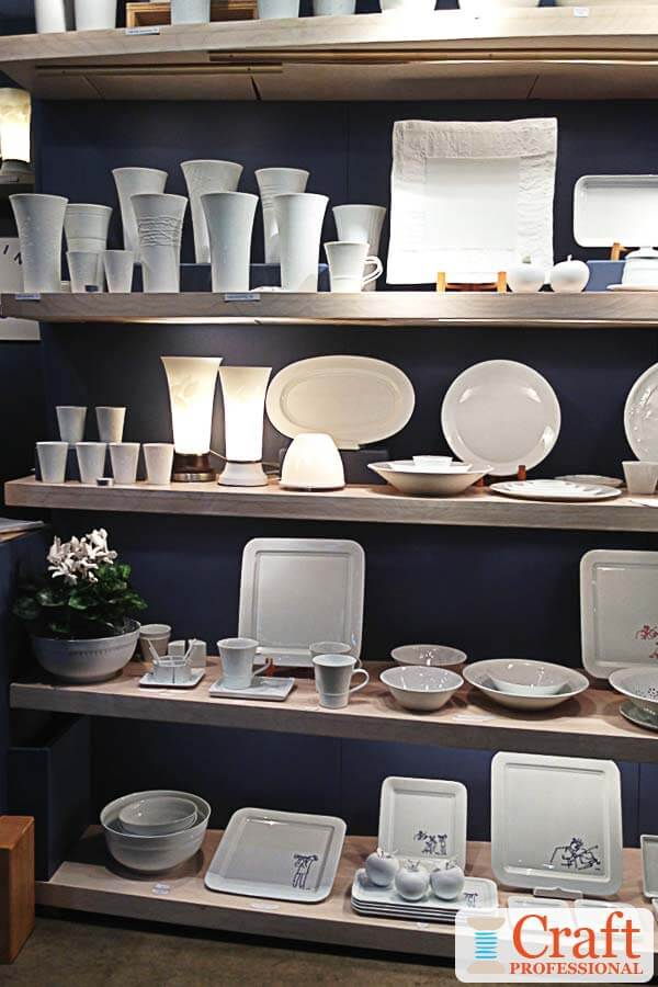 White, handmade tableware displayed in a craft booth on rows of light wood shelves with a midnight blue backdrop, and plenty of lighting under each shelf.