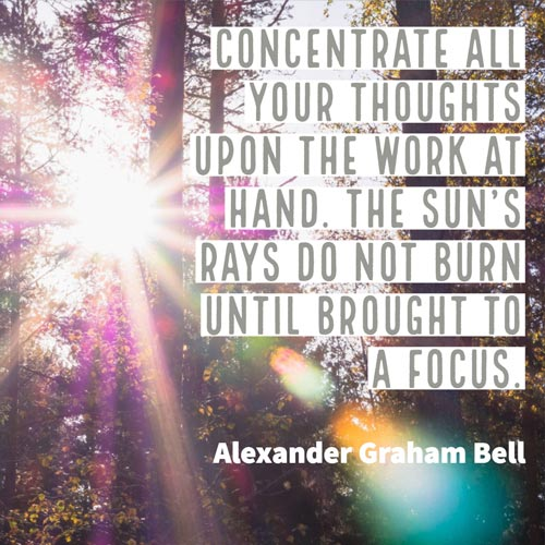 Sun rays through trees with text overlay - Concentrate all your thoughts upon the work at hand. The sun's rays do not burn until brought to a focus. Alexander Graham Bell