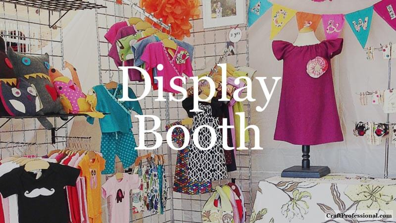 Colorful children's clothing on display at a craft show. Text overlay - Display Booth