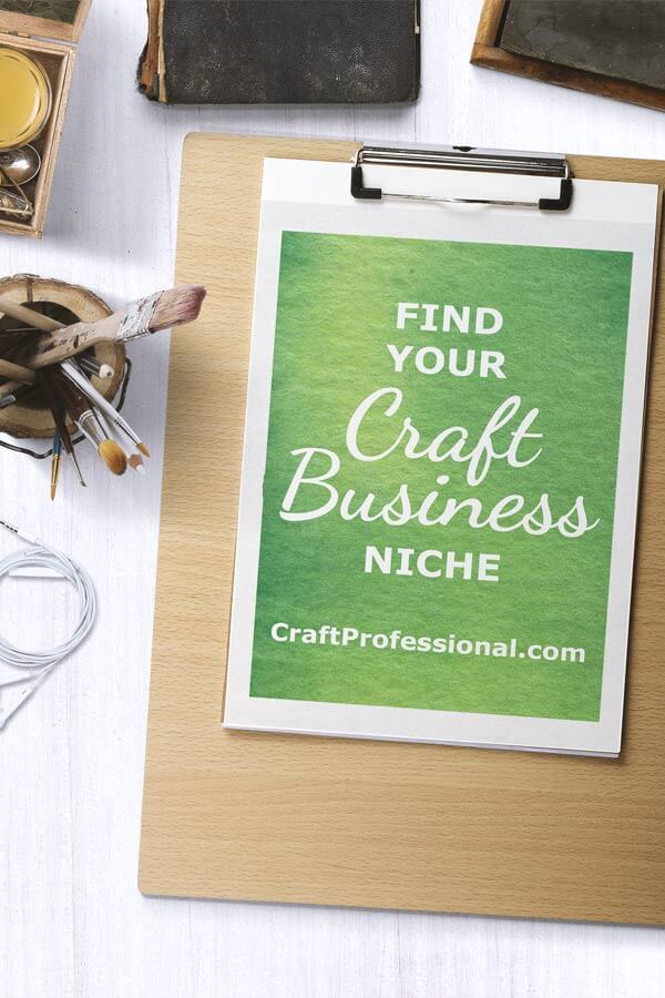 Desktop with paper on a wooden clipboard. Text on the paper reads: Find your craft business niche.