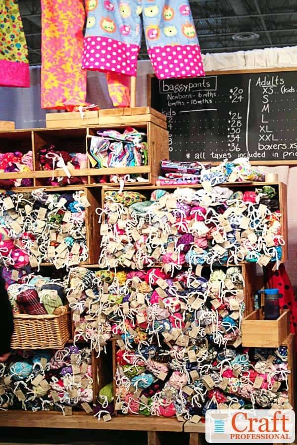 Multi-colored handmade pajamas casually displayed at a craft show in wooden crates and baskets.