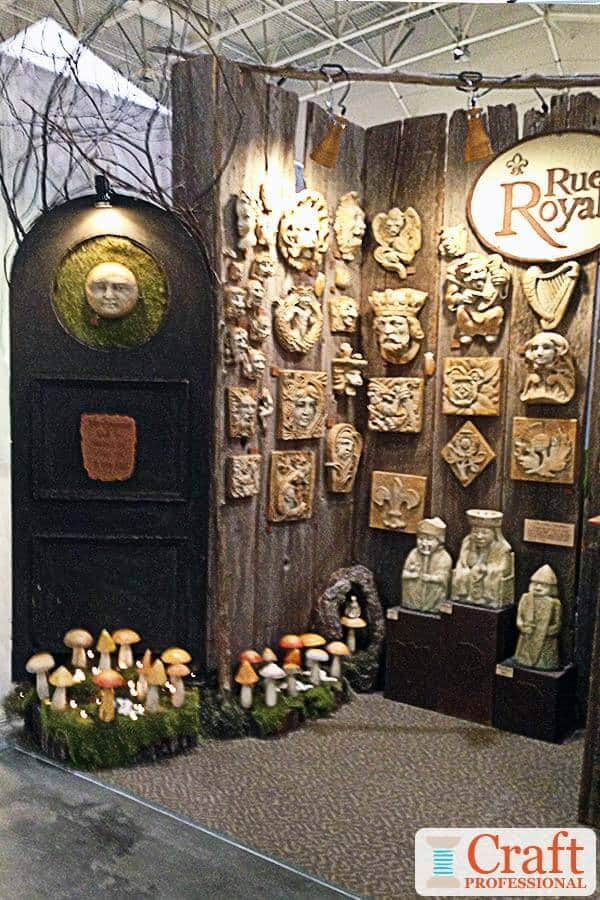 Garden decor displayed on a portable, rustic, wood fence at a craft show.