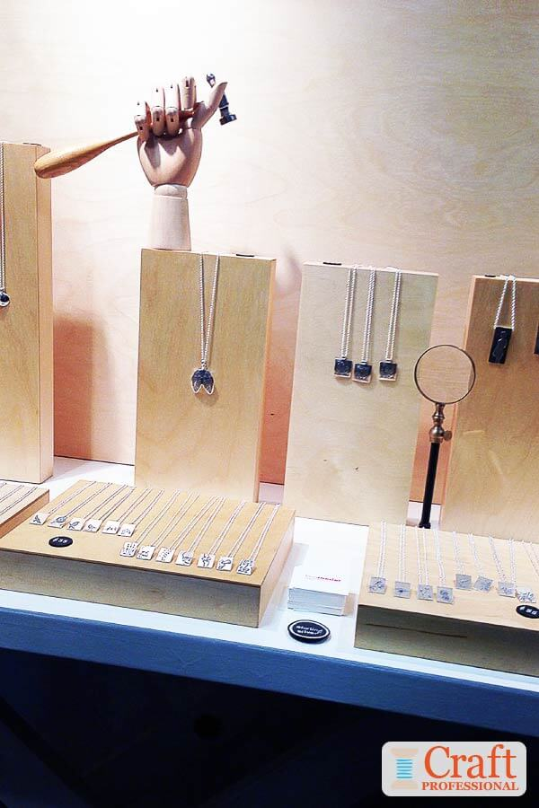 Handmade silver necklaces displayed on simple, wood blocks and stands.