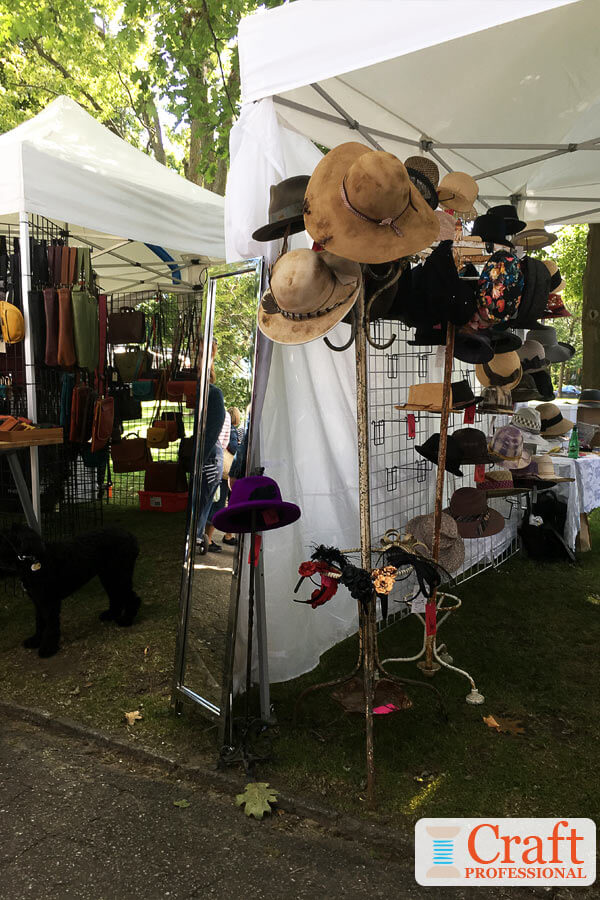 Handmade hats displayed on a millinery tree at an outdoor craft show.