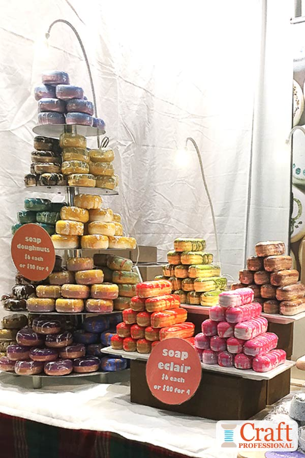 Handmade soap arranged in a pyramid shape on a tiered stand on display at a craft show.