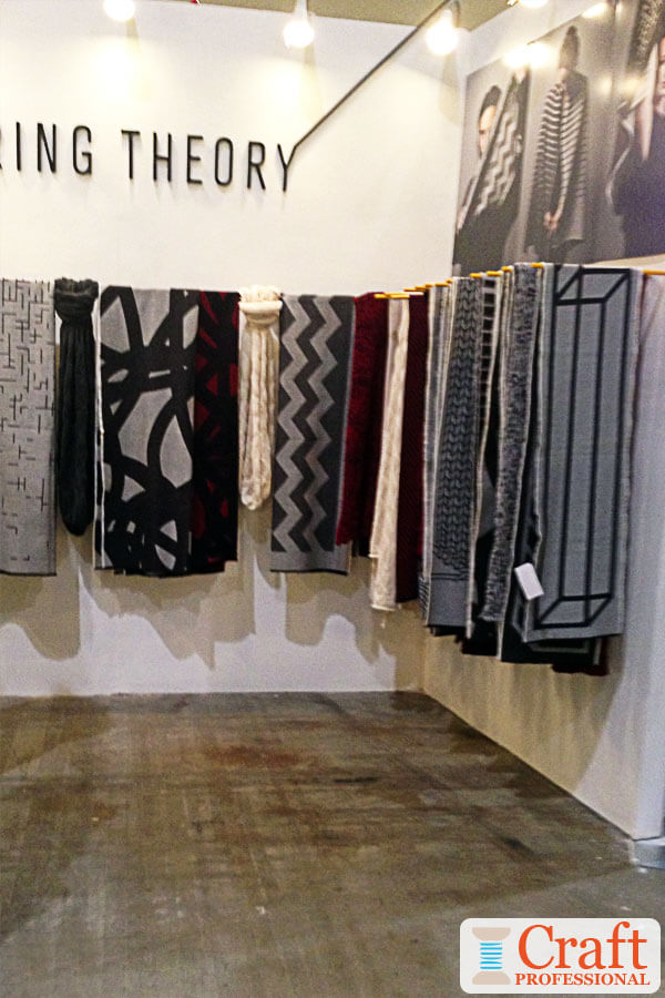 Black, white, and grey handmade shawls on display in a minimalist craft booth.