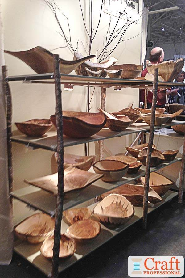 Handmade wooden bowls displayed on shelves at a craft show.