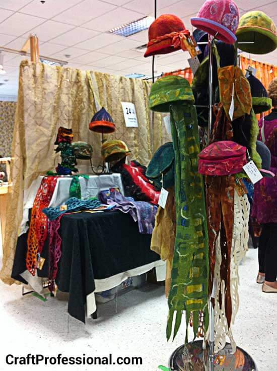 Handmade felted hats and scarves at a craft show