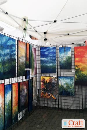 Paintings on display in a craft tent.