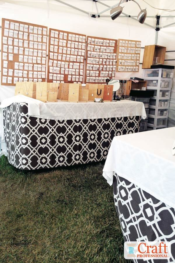 Handmade jewelry displayed on tabletops and shelves at an outdoor craft show. Tables are covered in graphic print black and white tablecloths..