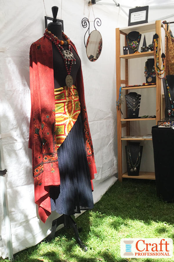 Dress form displaying handmade jewelry at the front corner of an outdoor craft booth helps to draw attention from a distance.