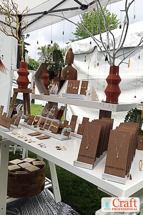 Handmade necklaces displayed on branches in a craft booth.