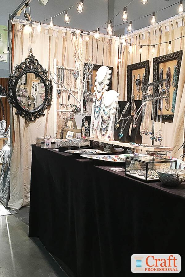 Handmade jewelry displayed on a table at a craft show. Strings of globe shaped lights are strung across the top, of the booth.
