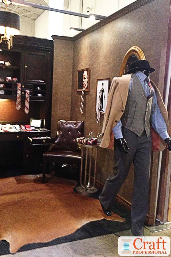 Male mannequin dressed in formal haberdashery attire in a masculine booth at a craft show.
