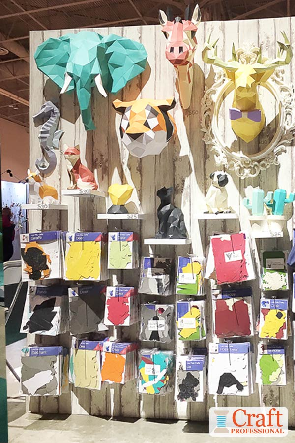 Handmade 3D paper animal heads on display at a craft show.