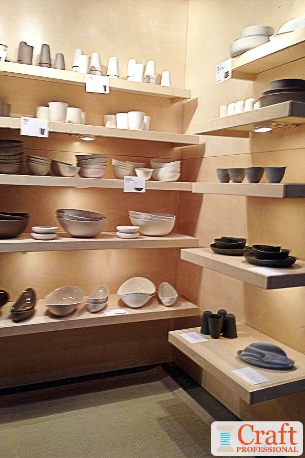 Neutral colored, handmade tableware displayed in a craft booth on rows of light wood shelves with lots of lighting under each shelf.