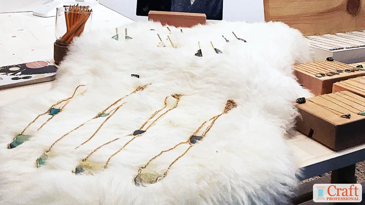 Handmade necklaces displayed on faux fur table covering.
