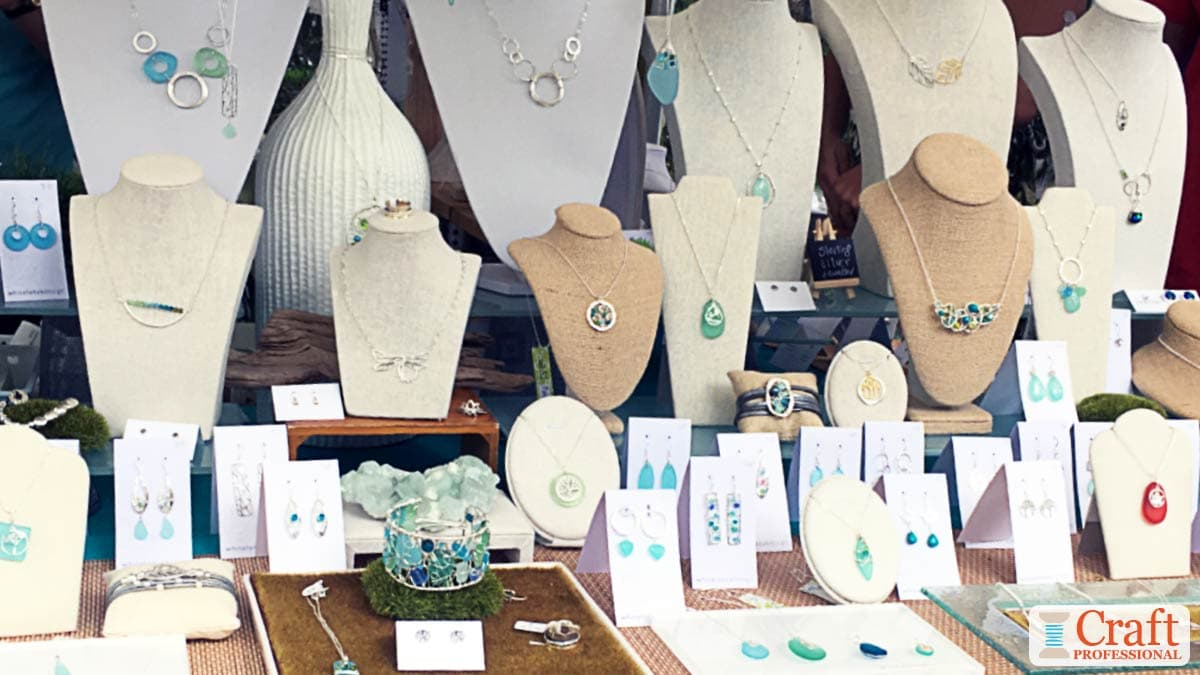 White and beige jewelry busts display handmade jewelry at a craft fair.