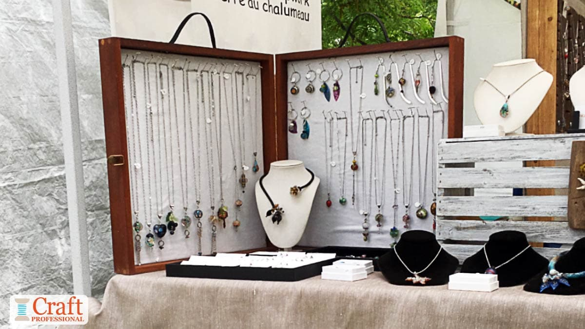 Handmade necklaces displayed in a portable jewelry display case.